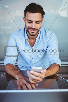 Smiling businessman using phone while working on laptop