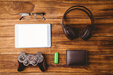 Tablet and glasses next to joystick music headphone and wallet