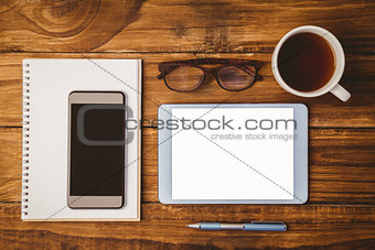 Smartphone on notepad next to tablet and glasses and cup of coffee