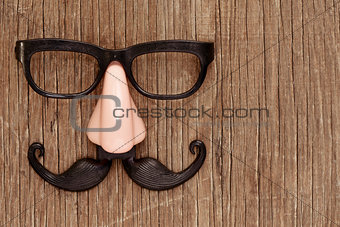 fake mustache, nose and eyeglasses on a wooden surface
