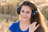 Girl listening to music in  field