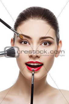 Beautiful girl with makeup brushes