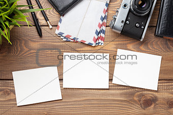 Blank photo frames, camera and supplies on table