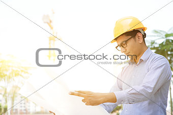 Asian Indian male contractor engineer reading blueprint