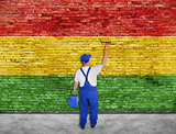 House painter paints Reggae flag on brick wall