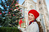 Woman with gift box standing near Christmas tree in Florence