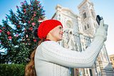 Woman tourist taking photo near Christmas tree in Florence