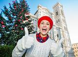 Woman traveler showing thumbs up in Christmas decorated Florence
