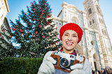 Traveler holding photo camera near christmas tree in Florence