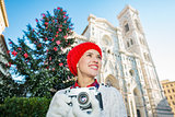 Woman holding photo camera near christmas tree in Florence