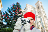 Happy woman holding photo camera near christmas tree in Florence