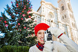 Happy woman traveler making photos of Christmas in Florence