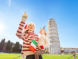 Mother in Christmas hat pointing on to daughter. Pisa, Italy