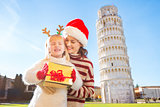 Woman in Christmas hat and baby girl holding gift box. Pisa