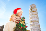 Woman and baby girl holding Christmas tree. Pisa, Italy