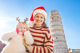 Happy mother and daughter spending Christmas time in Pisa, Italy