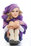 Girl dressed in a bright purple knitted scarf and hat.