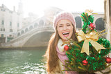 Woman with Christmas tree near Rialto Bridge in Venice, Italy