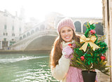 Smiling woman with Christmas tree near Rialto Bridge in Venice
