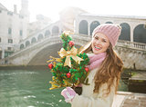 Young woman with Christmas tree near Rialto Bridge in Venice