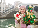 Happy woman with Christmas tree and gift box in Venice, Italy