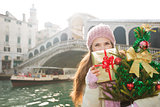Young woman with Christmas tree and gift box in Venice, Italy