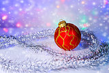 Red Christmas-tree ball and tinsel. Christmas decorations.