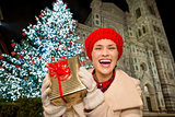 Woman showing gift box near Christmas tree in Florence, Italy