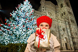 Happy woman with gift box near Christmas tree in Florence, Italy