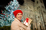 Marry woman with gift box near Christmas tree in Florence, Italy