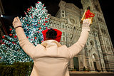 Woman with gift box rejoicing near Christmas tree in Florence