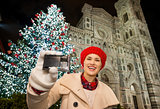Happy woman showing photo camera near Christmas tree in Florence