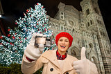 Woman showing camera and thumbs up in Christmas Florence, Italy