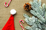 Christmas decorations: top view of candy canes, cones, Santa cap and pine branch on linen fabric background