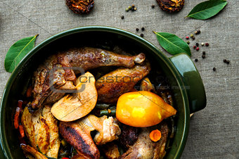 Top view of fried and baked chicken with vegetables in round ceramic stew pot on linen fabric background
