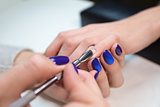 Woman in salon receiving manicure by beautician