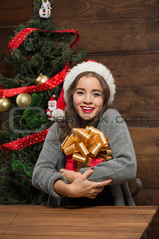 Beautiful girl sitting at the table with a present near New Year tree