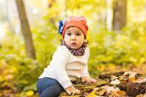 Cheerful little girl on a stump in the woods of autumn park