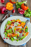 Vitamin salad with persimmon, cheese and pomegranate seeds.
