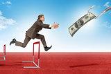 Man hopping over treadmill barrier with dollar