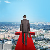 Businessman walking on red arrow above city