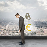 Businessman with key in back and euro sign