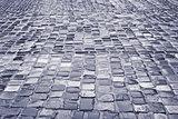 Road with wet cobblestones in rainy weather