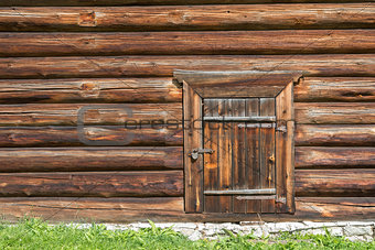 Old log house wood wall with closed door and padlock