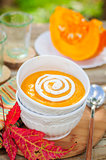 Pumpkin Cream Soup with Sour Cream in a White Bowl