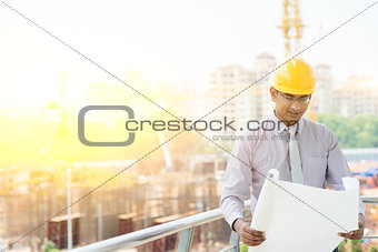 Asian Indian male site contractor engineer inspecting at site