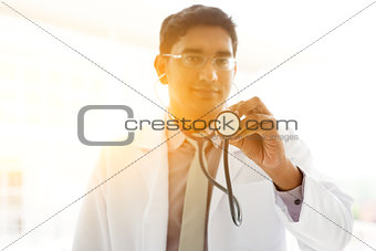 Asian Indian medical doctor holding stethoscope