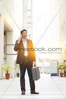 Asian Indian businessman full length using smartphone