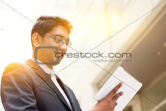 Asian Indian businessman using tablet computer