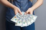 Fan of 100 dollar banknotes in woman hands